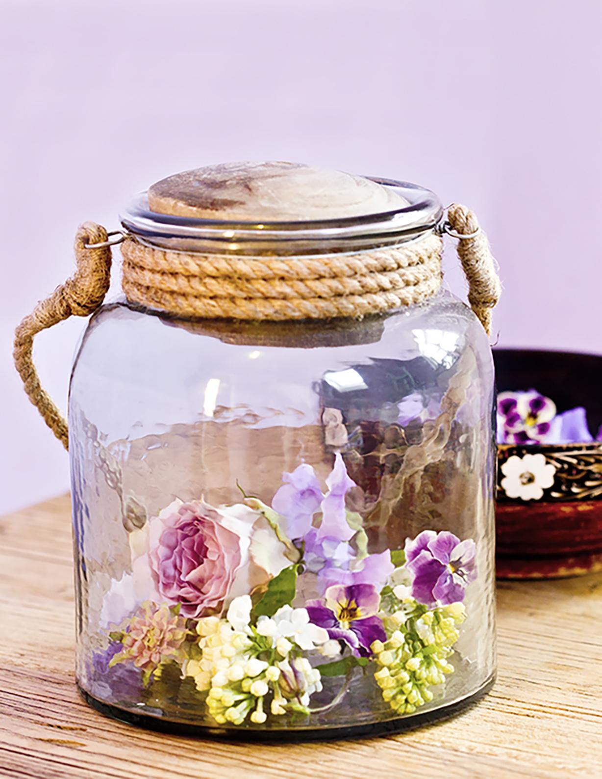 """Du kan pynte op med andet end buketter. Læg små blomsterhoveder fra syrener, roser, stedmor og ærteblomster i bunden af glas, lanterner eller vaser. Fugt bunden i glasset med en vandforstæver - og nyd en anderledes """"buket""""."""