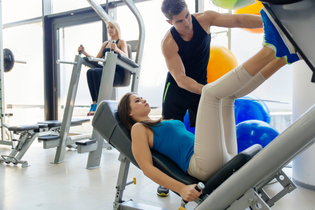Beautiful woman doing leg exercises in gym with the help of personal trainer