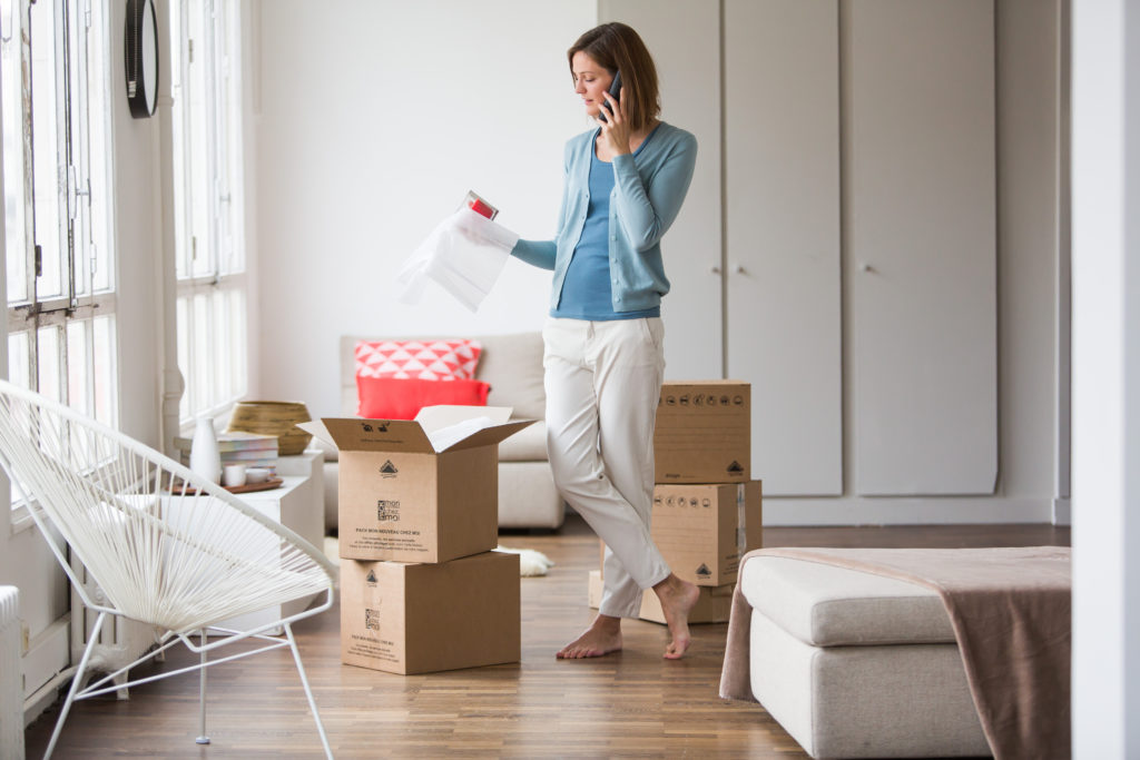 Model Released - Woman carrying moving boxes in her new home.