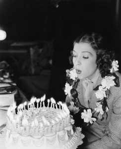 Profile of a young woman blowing off candles on a birthday cake (EV005818_H)
