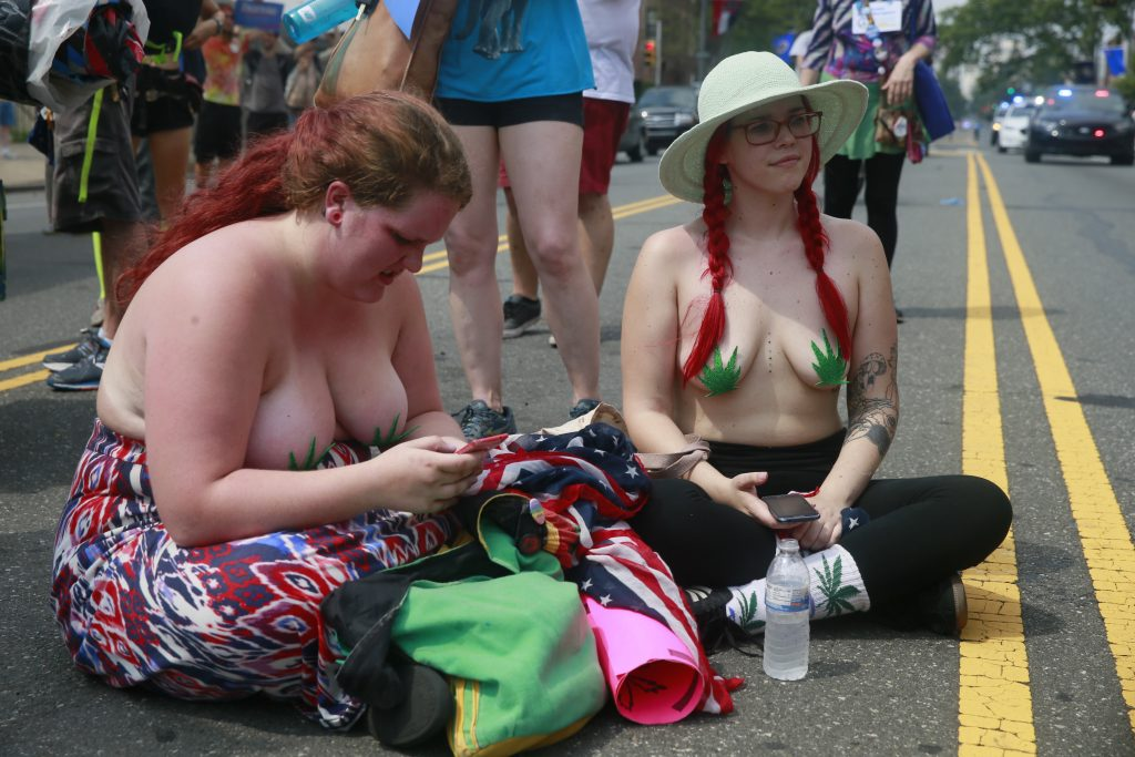 July 25, 2016 - Philadelphia, Pennsylvania, United States: Supporters of Bernie Sanders march from City Hall to FDR park on the first day of the Democratic National Convention. Two women in support of the legalization of marijuana wear leaf shaped pasties over their breasts. (Jeremy Hogan/Polaris)