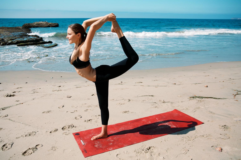 Kvinde laver yoga på en strand (Foto: All Over)