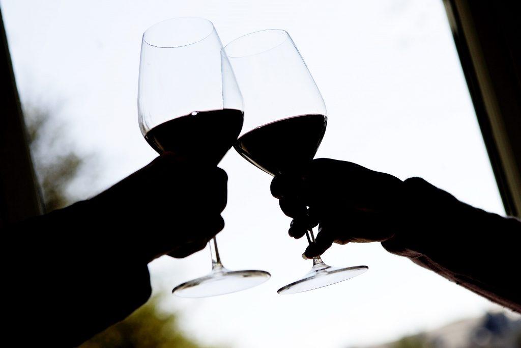 To mennesker skåler med rødvin i glas. (Foto: Polfoto)