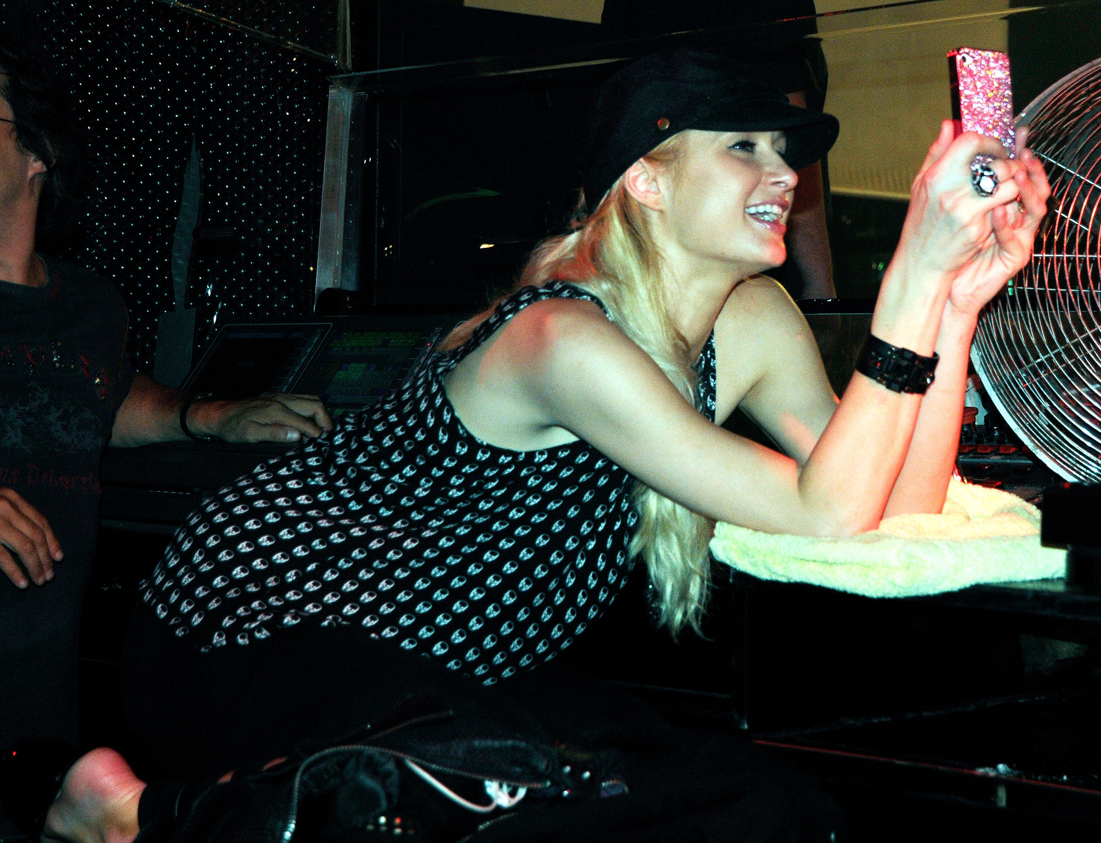 Paris Hilton står med sin telefon til en fest (Foto: All Over)