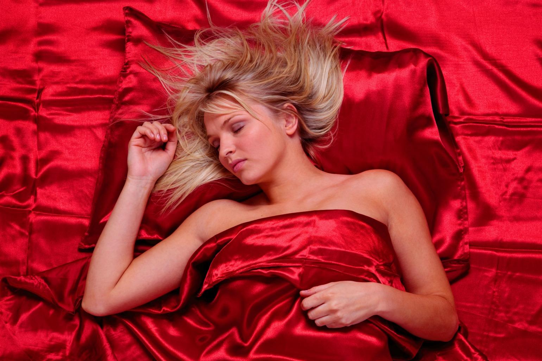 Pige ligger i rødt silke sengetøj (Foto: All Over)