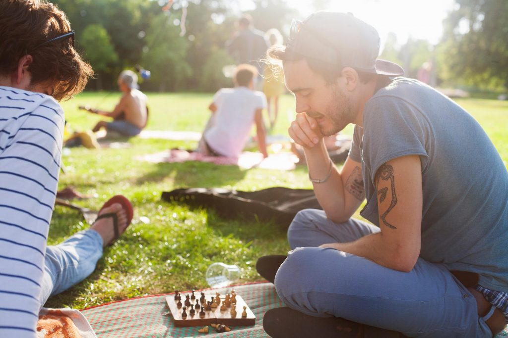 brætspil, brætspillets dag, skak, ung mand, fyr, park, have, sidder på græsset, kasket, solnedgang, park, hygge