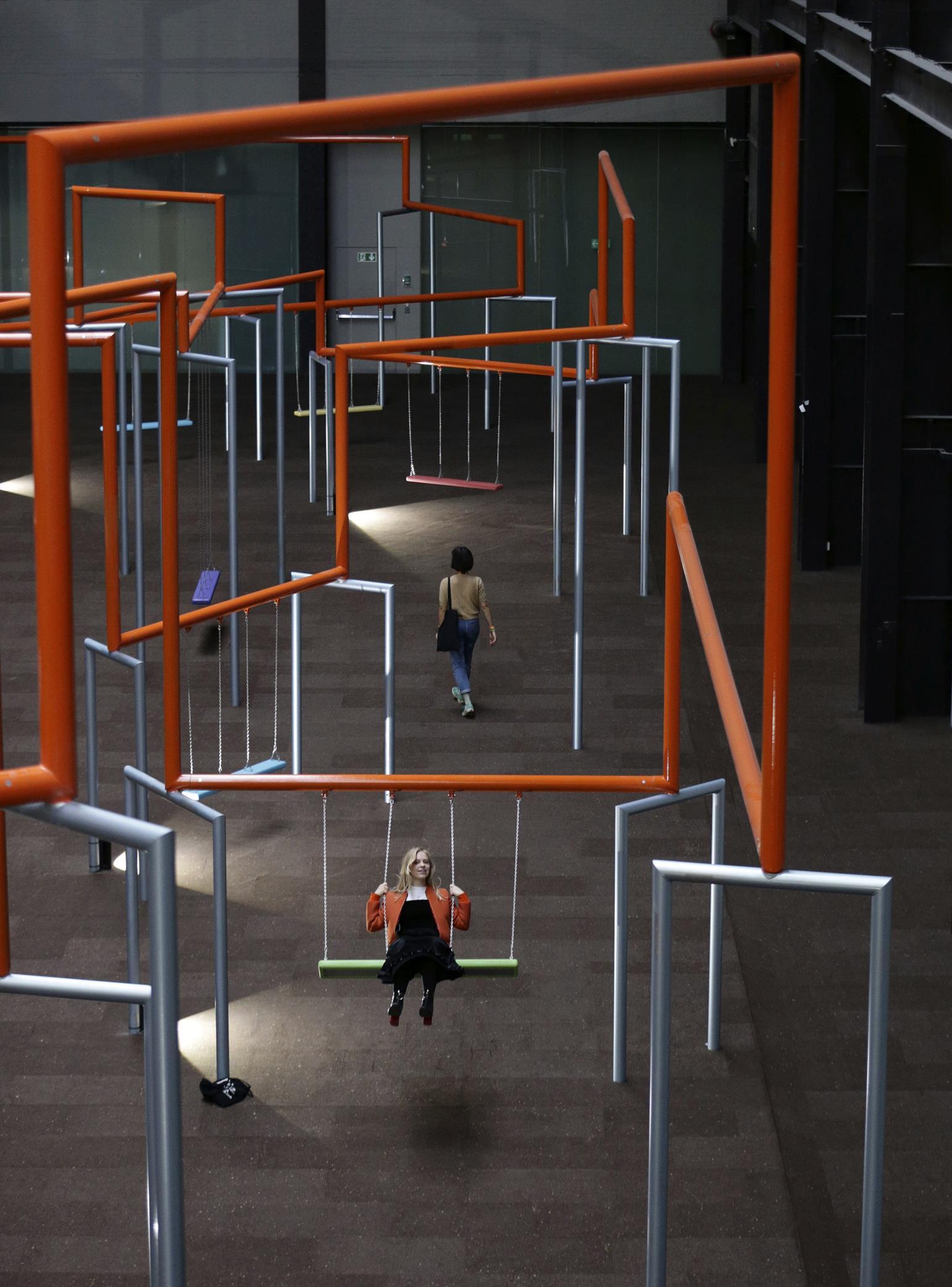 En besøgende sidder på en gynge, som er en del af den store, interaktive kunstinstallation, som den danske gruppe SUPERFLEX udstiller på Tate Modern i London. (Foto: /ritzau/)