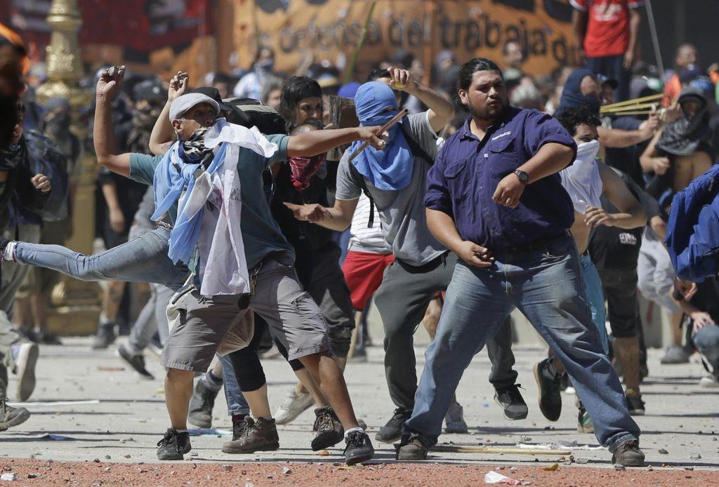 Demonstranter kaster ting på politiet i massestrejken mod pensionsreformen i Argentina. Fagforeningsledere klager over ordningen, der allerede er gået gennem senatet, og som vil skære i pensionsudbetalingen og hjælpen til nogle fattige familier. (Foto: /ritzau/)