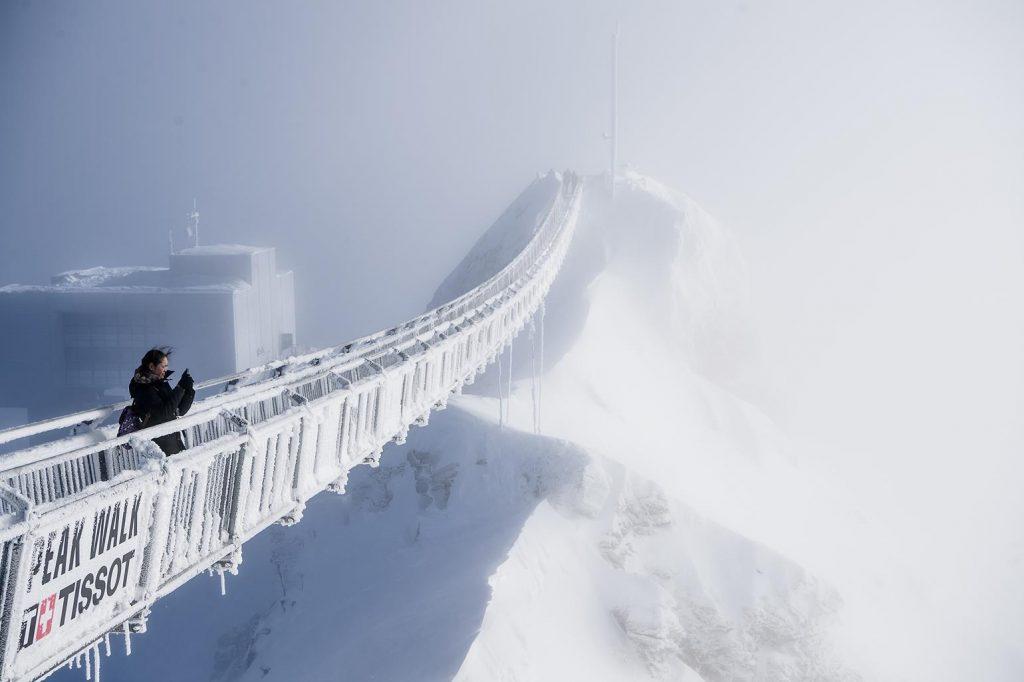 En turist står på Peak Walk-hængebroen på Glacier 3000 på bjergpasset Col du Pillon i Schweiz' vintervejr. (Foto: /ritzau/)