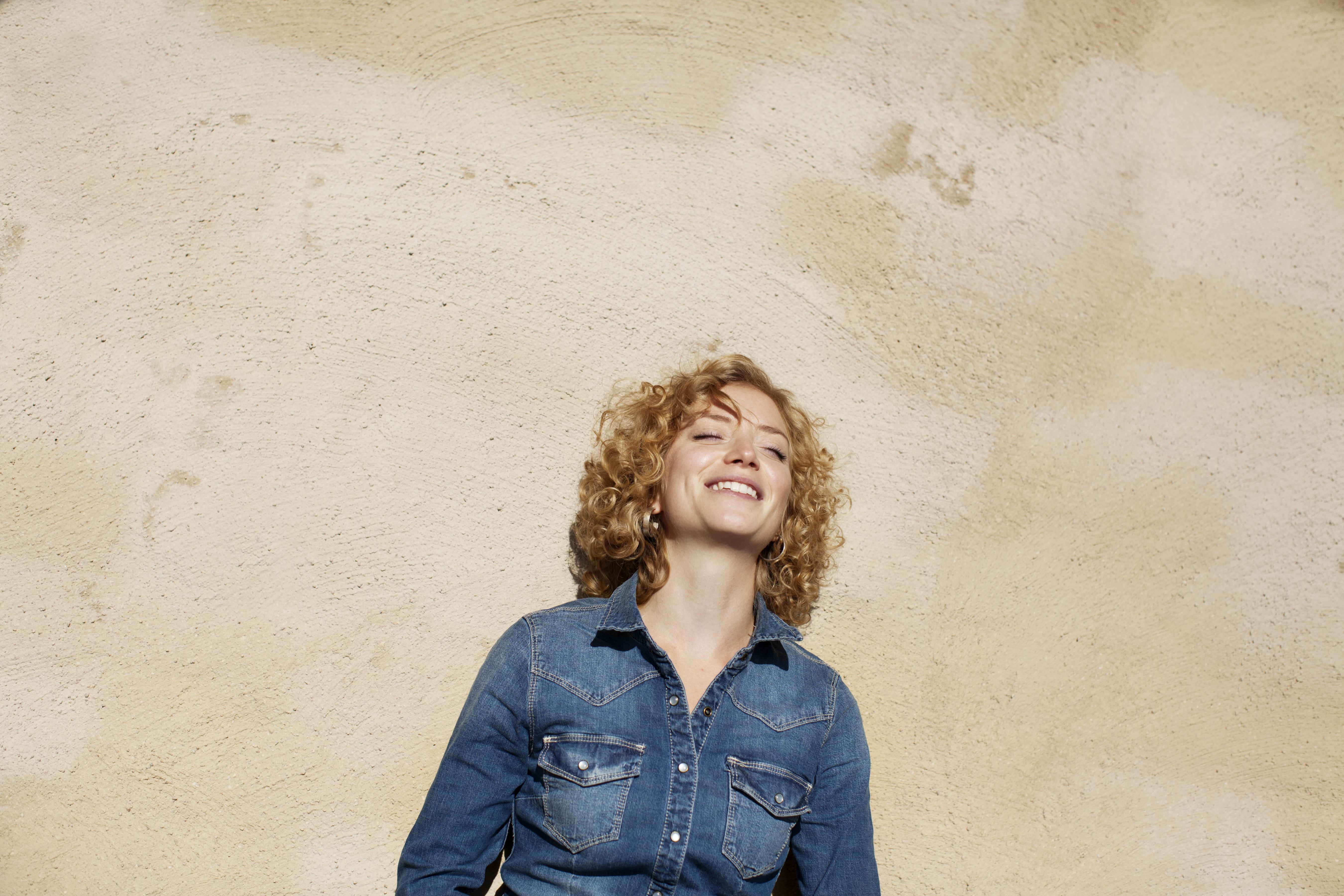 Ung kvinde som smiler i solen og mediterer mindfulness
