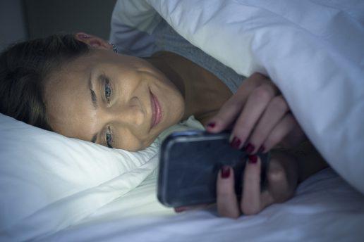 Kvinde ligger i sin seng og bruger netdating på sin iPhone.