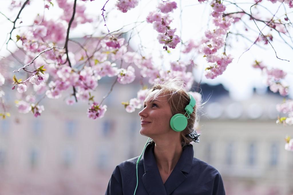 Kvinde står med høretelefoner på under et kirsebærtræ og lytter til Spotify - hun bruger sandsynligvis den smarte viralliste
