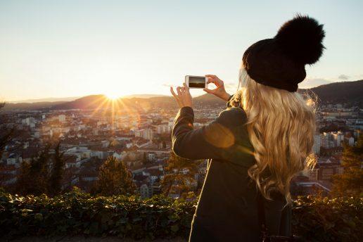 Kvinde tager foto og bruger rejseapps i Østrig