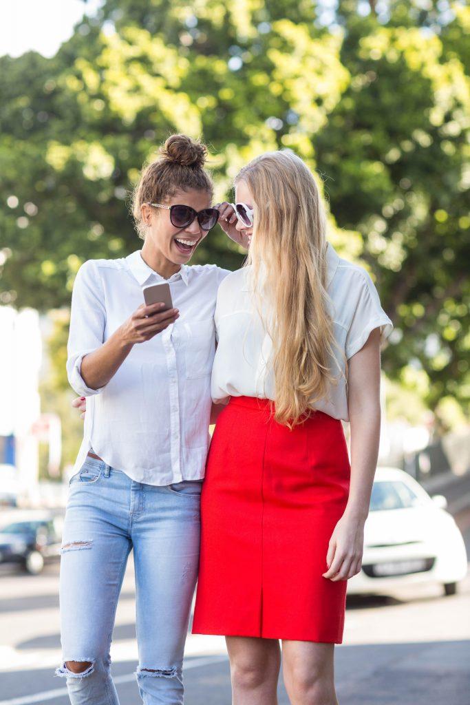 To veninder griner på gaden, den ene har en smartphone i haanden
