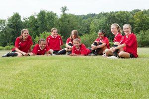 pigegruppe spiller fodbold sammen og hygger bagefter på græsset (Foto: All Over)