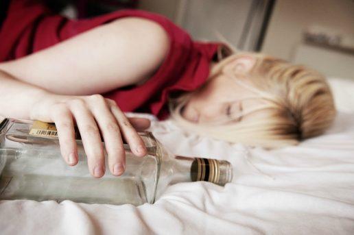 Pige har tømmermænd d. 1. januar og ligger i sengen med en alkohol flaske (Foto: All Over)