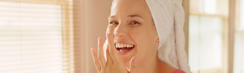 Pige tager creme på på badeværelset med håndklæde om håret (Foto: All Over)