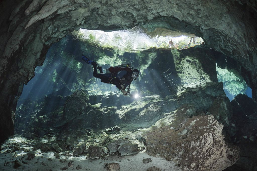 diver in the cave of Gran Cenote, Mexico, Yucatan, Tulum, krystalklart vand