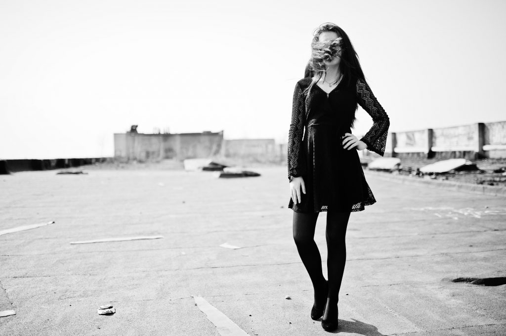 Portrait brunette girl with red lips wearing a black dress, tights and shoes on heels posed on the roof. Street fashion model.