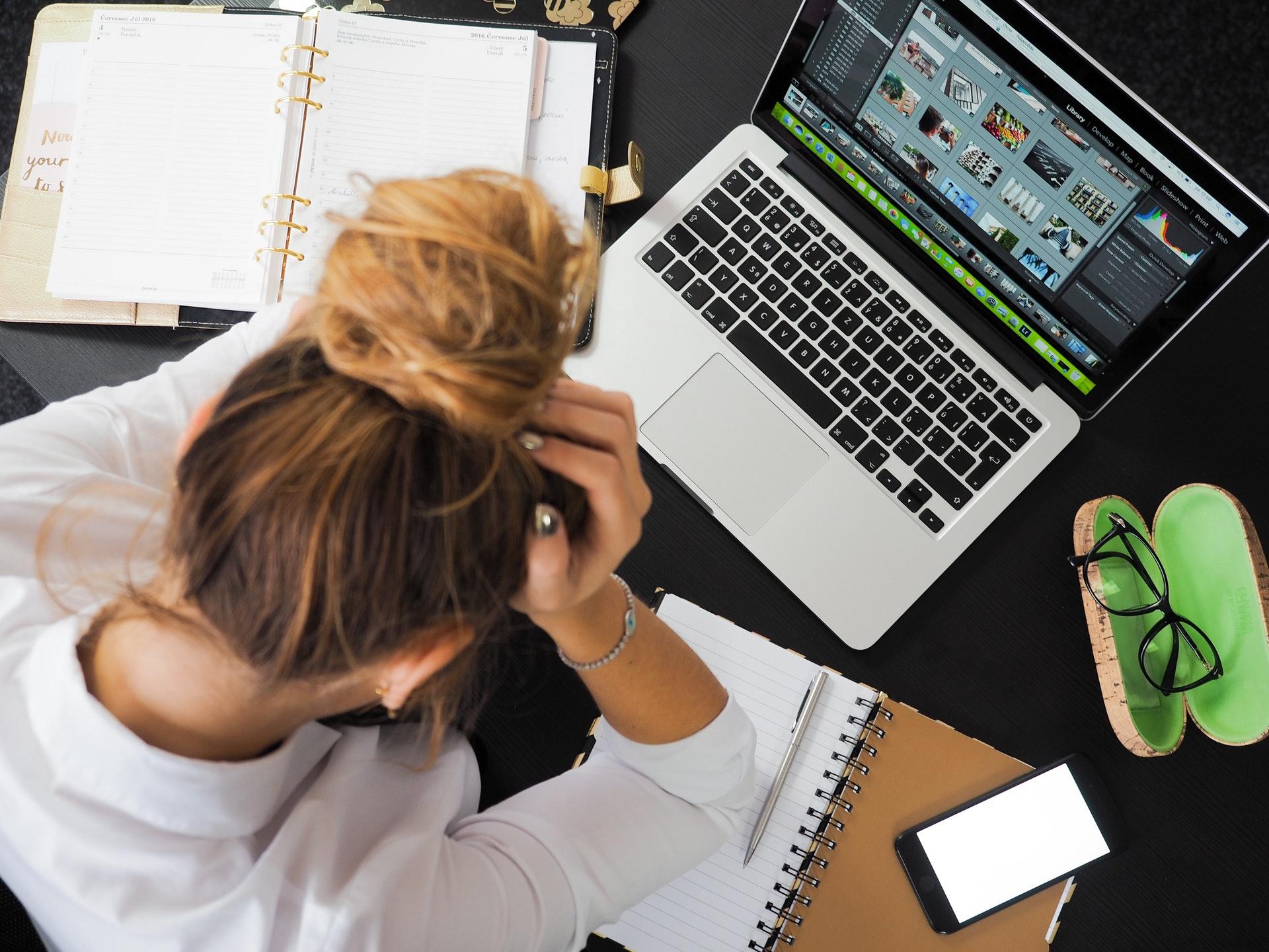præstationskultur, stress, arbejde, resultater, computer, bærbar, mac, skrivebord, kvinde, tager sig til hovedet, opgaver, lektier, arbejde