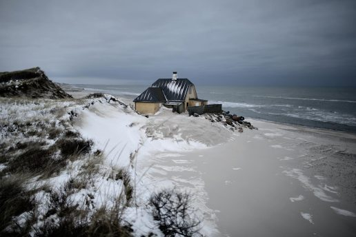 2014: Havet æder mere og mere af den nordjyske kyst, og fotografen bag dette billede beskriver sommerhuset som mere eller mindre forladt, mens der er blevet forsøgt at standse vandet med sandsække. (Foto: /ritzau/)