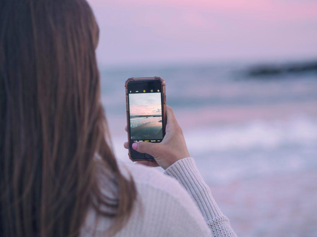 pige mobil strand rejse (Foto: Unsplash - Aaron Burden)