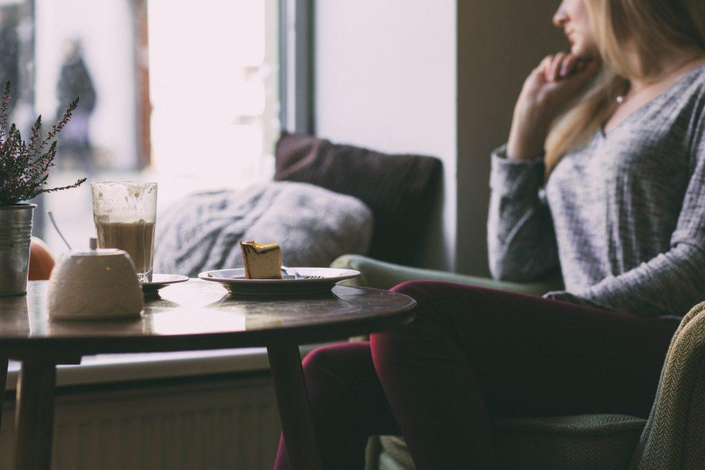 pige kage kaffe tænker vindue hygge (Foto: Unsplash)