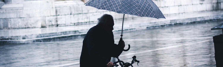 ældre mand pension regn cykle paraply (Foto: Unsplash)