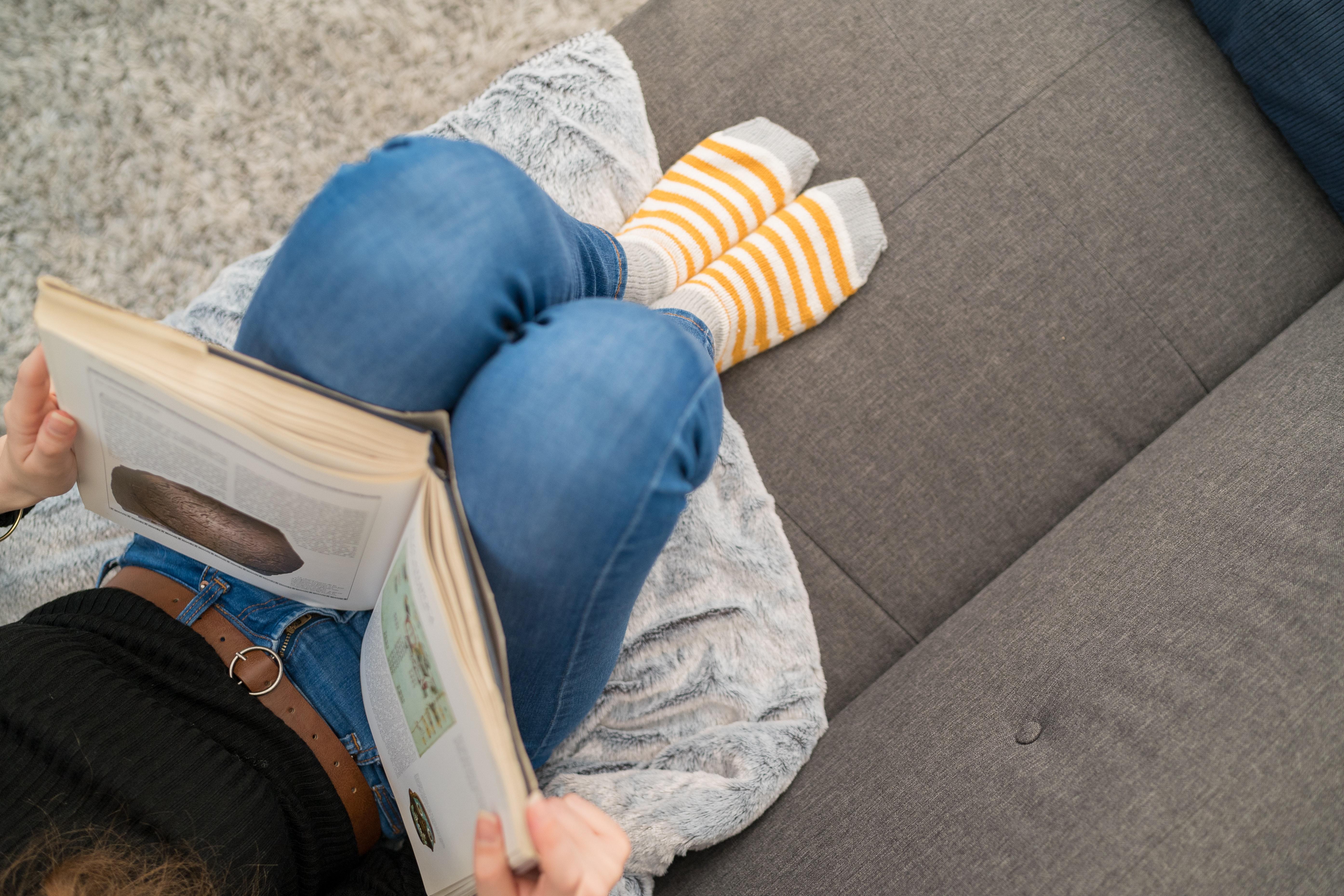 Bog, pige, læsning, sokker, sofa, hygge. (Foto: Unsplash)