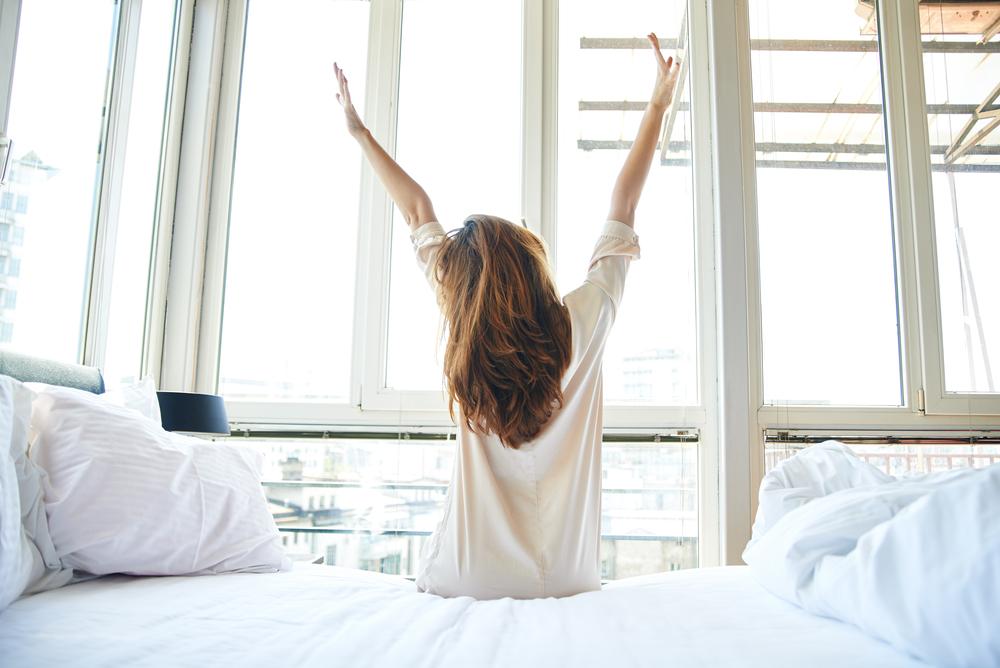 pige strækker sig vindue seng (Foto: Shutterstock)