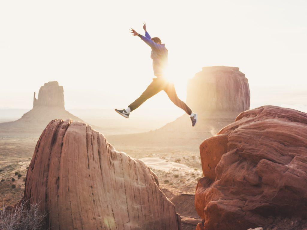 hoppe glad pige springe bjerg (Foto: Unsplash)